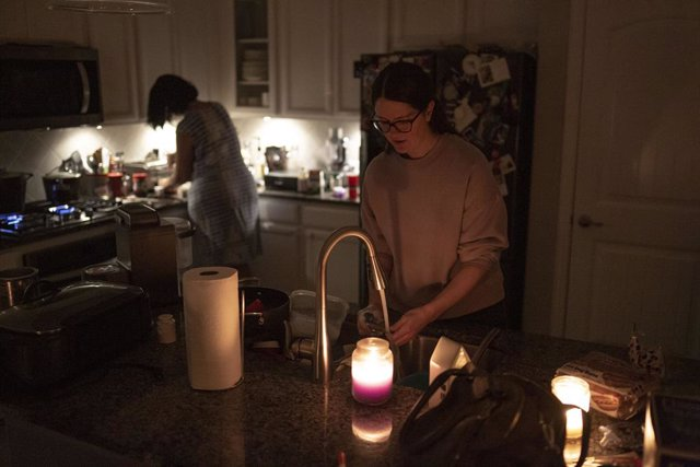 15 February 2021, US, Argyle: Women work in a kitchen lit by candles as millions in Texas are without power after a winter storm slammed the state. Photo: Chris Rusanowsky/ZUMA Wire/dpa