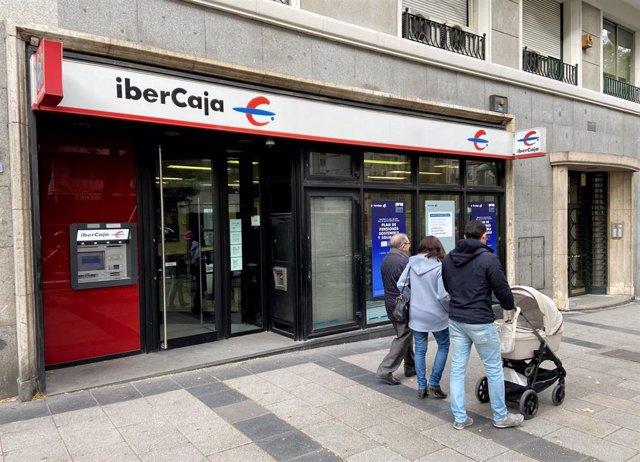 Archivo - Una familia pasea junto a una oficina de IberCaja en Madrid.