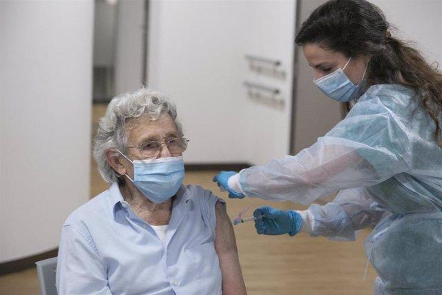Archivo - Una sanitaria vacuna contra la Covid-19 a un usuario de una residencia de Gijón.