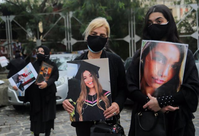 04 February 2021, Lebanon, Beirut: Families of those who were killed in 4th of August Beirut port blast carry pictures of their beloved ones as they attend a silent sit-in at the entrance of the port to mark six months after of the blast that killed more
