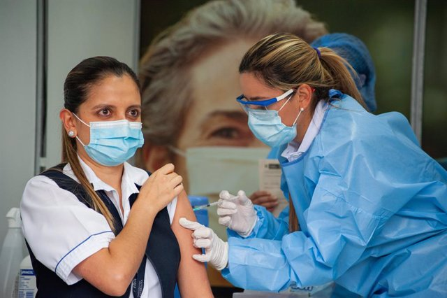 18 February 2021, Colombia, Bogota: A health worker receives a dose of Pfizer-BioNtech's Covid-19 vaccine at the start of the Coronavirus vaccination campaign in nine hospitals. Atotal of 12,582 doses of Pfizer-BioNtech's Covid-19 vaccine were distribute