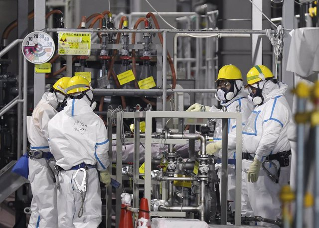 Archivo - 22 January 2020, Japan, Okuma: Fully covered workers check water processing system ALPS(Multi-nuclide retrieval equipment) where process contaminated water to store in tanks at ALPS' house of tsunami-devastated Tokyo Electric Power Company (TEPC