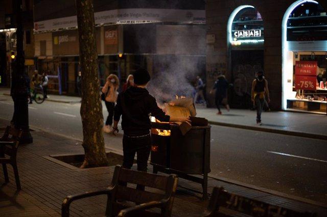 Un activista crema una paperera de la Rambla de Barcelona en els disturbis en suport al raper Pablo Hasel