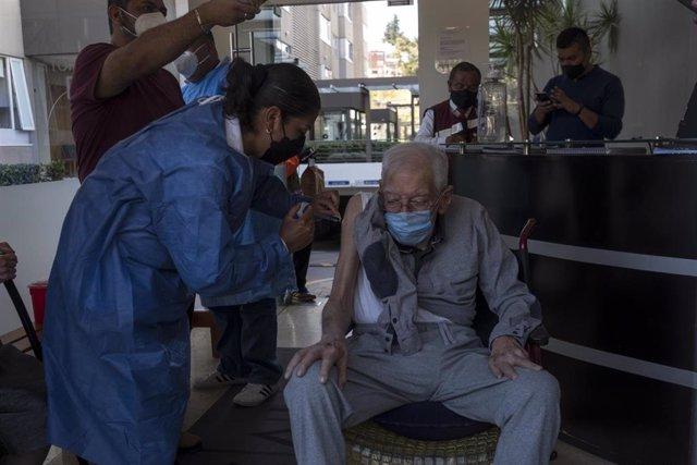 La enfermera Elena Tello vacuna con una dosis de la vacuna AstraZeneca a un hombre mayor.