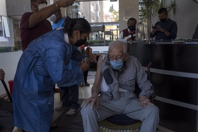 18 February 2021, Mexico, Mexico City: Nurse Elena Tello vaccinates an elderly man with a dose of AstraZeneca coronavirus vaccine. City medical workers come to an elderly residence to administer people who do not have the opportunity to visit vaccination