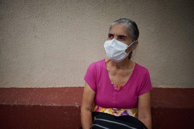 Mujer brasileña espera vacunarse