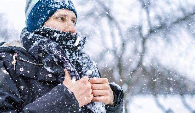 Hombre abrigado con frío bajo la nieve.