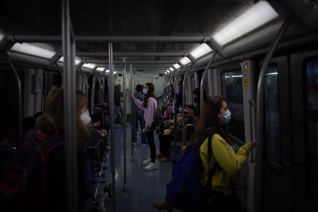 Archivo - Arxiu - Diverses persones viatgen en metro a Barcelona, en el primer matí després del toc de queda a la ciutat, a Barcelona, Catalunya (Espanya), el 26 d'octubre del 2020