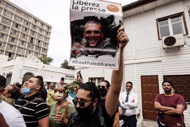 Archivo - 21 September 2020, Algeria, Algiers: A man holds up a poster bearing the picture of Algerian journalist Khaled Drareni during a solidarity rally at the Tahar Djaout Press House. Drareni, who has been under arrest since 29 March 2020, received a