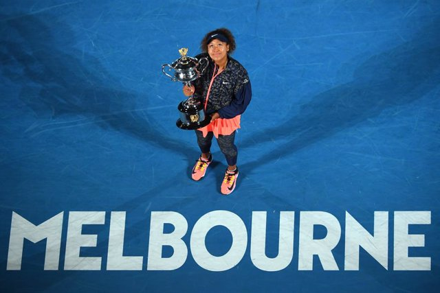 Naomi Osaka of Japan holds the trophy after winning the women's singles final against Jennifer Brady of the United States on day 13 of the Australian Open tennis tournament at Rod Laver Arena in Melbourne,, Saturday, February 20, 2021. (AAP Image/James Ro
