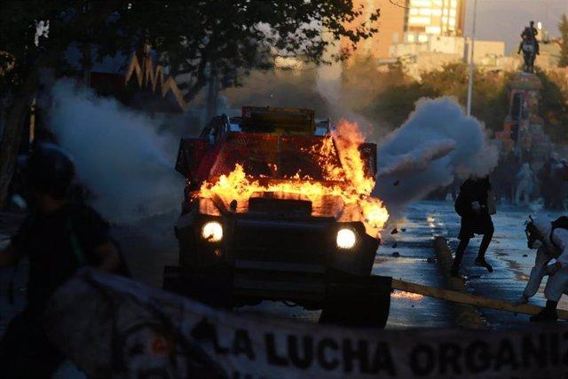 Un vehículo de Carabineros incendiado durante las protestas sociales en Chile