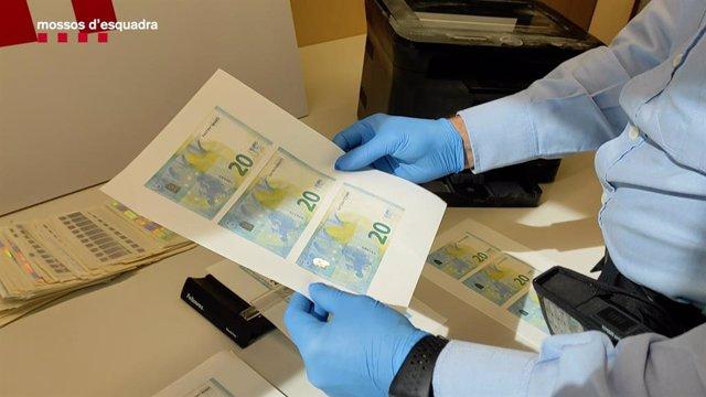 Fulles de paper amb bitllets falsos de 20 euros impresos.