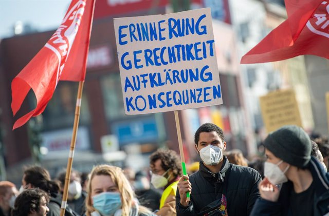 """20 February 2021, Berlin: A participant holds a placard reading """"Remembrance - Justice - Clarification - Consequences"""" during a demonstration to commemorate the victims of the right-wing extremist attack in Hanau on 19 February 2020. Photo: Christophe Gat"""