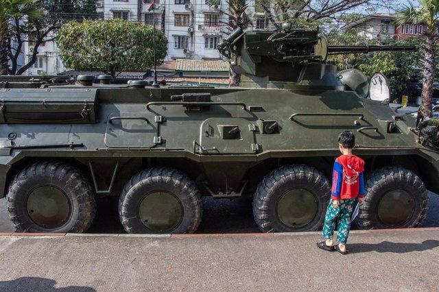 Un niño juega junto a un vehículo militar en Rangún