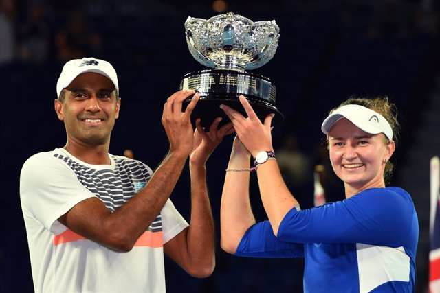 Barbora Krejcikova of the Czech Republic and Rajeev Ram of the United States raise the trophy after winning the mixed doubles final against Matthew Ebden and Samantha Stosur of Australia on day 13 of the Australian Open tennis tournament at Rod Laver Aren
