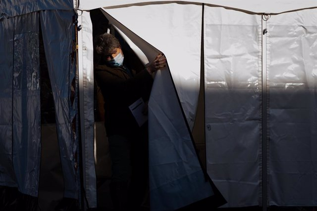 10 February 2021, United Kingdom, London: A man emerges after getting a Covid-19 test at a mobile testing unit at the Waylett Place car park, London after a case of the South African variant was discovered in the area. Photo: Aaron Chown/PA Wire/dpa