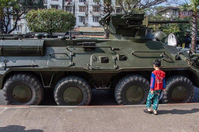 Un nen juga al costat d'un vehicle militar a Yangon