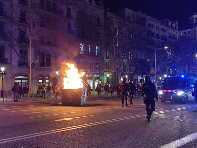 Cremen un contenidor en el passeig de Gràcia de Barcelona durant la manifestació en suport a Pablo Hasel
