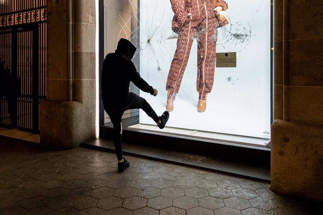 Un jove dóna una puntada contra l'aparador d'una botiga durant una manifestació contra l'empresonament de Pablo Hasel, a Barcelona