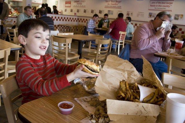 Archivo - Niño comiendo comida basura