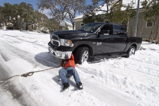 15 February 2021, US, Austin: A motorist tries to hook a chain to his truck stuck for several hours in downtown Austin after a rare snowstorm overnight in central Texas. Austin is shut down waiting for a temperature rise later this week. Photo: Bob Daemmr