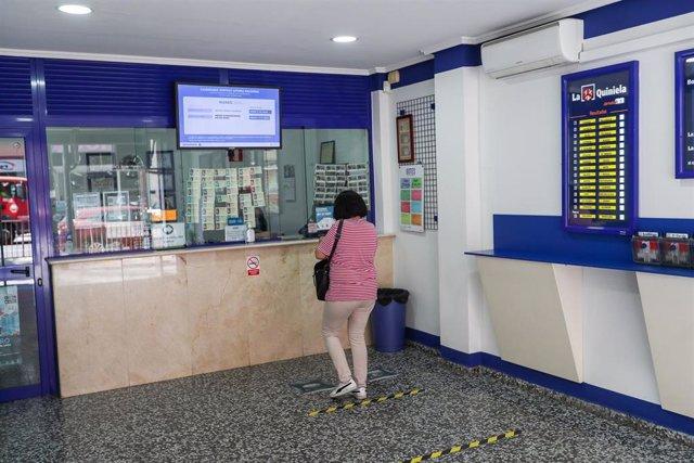 Archivo - Una mujer compra lotería en una Administración