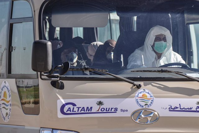Archivo - 03 February 2020, Algeria, Algiers: Passengers, from Algeria, Libya and Mauritania, wearing surgical masks, leave on a transport bus at the the Houari Boumediene Airport, after arriving on an Algerian air plane following their evacuation from Ch