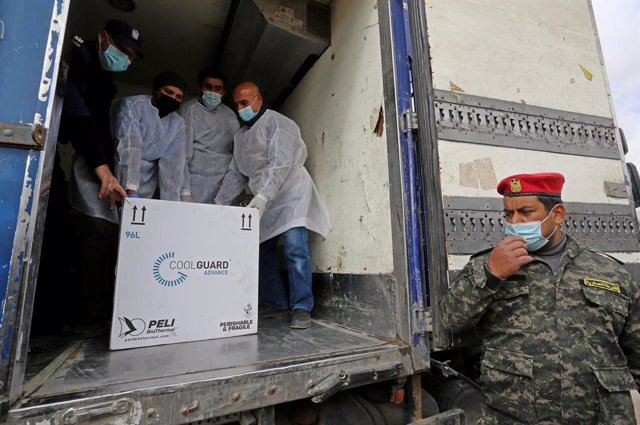 17 February 2021, Palestinian Territories, Rafah: Palestinian health workers unload the first arriving shipment of the Sputnik V COVID-19 vaccine on the Palestinian side of the Kerem Shalom border crossing south of Rafah. Photo: Ashraf Amra/APA Images via
