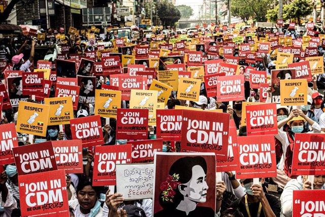 Manifestantes contra el golpe de Estado en Rangún con pancartas de apoyo al movimiento de desobediencia civil, CDM por sus siglas en inglés