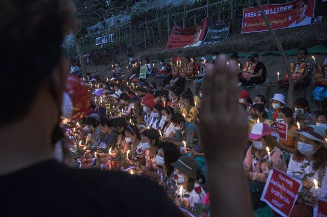 21 February 2021, Myanmar, Yangon: A man give three-finger salute during the candle-light vigil protest against the military coup near Embassy of the United States of America in Yangon. Photo: Thet Htoo/ZUMA Wire/dpa