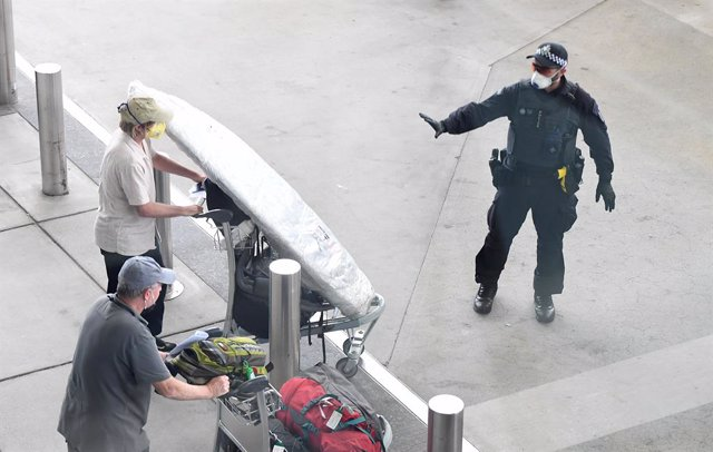 Archivo - A police officer instructs a returning passenger to stop after arriving on a special Nepal Air flight repatriating Australian and New Zealanders from overseas, in Brisbane airport, Thursday, April 2, 2020. The chartered flight out of Nepal had 2