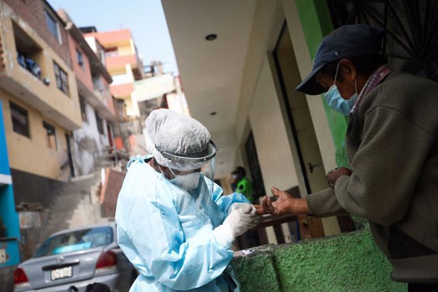 Archivo - 20 August 2020, Peru, Santa Anita: A health worker takes a blood sample from a man for the coronavirus test during a door-to-door testing campaign. Photo: Jhonel Rodríguez Robles/Agentur Andina/dpa