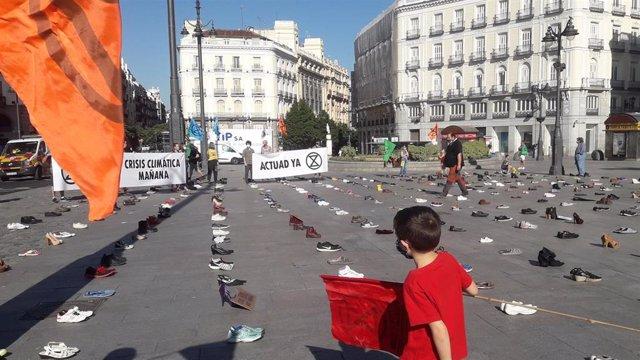 Archivo - Un niño sostiene una pancarta de Extinction Rebellion en la Puerta del Sol de Madrid, que aparece cubierta de zapatos, en una iniciativa del movimiento internacional de desobediencia civil pacífica en plazas icónicas de varias ciudades españolas