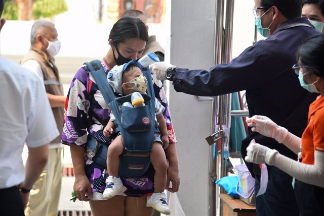 Archivo - 23 April 2020, Thailand, Bangkok: A baby has his temperature checked as a protective measure against the Coronavirus (Covid-19) before entering the Wat Rakhangkhositaram Woramahaviharn monastery where Thai monks distribute food aid amid the Coro