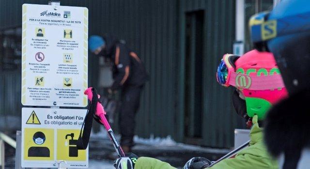 Dos esquiadors consulten la mesures de seguretat a l'estació d'esquí de La Molina (Girona) per evitar contagis de covid-19.