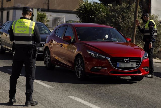 Un policía local ordena detenerse a un coche en un control en el límite entre los municipios de Murcia y Santomera, en Murcia (España) a 13 de febrero de 2021.