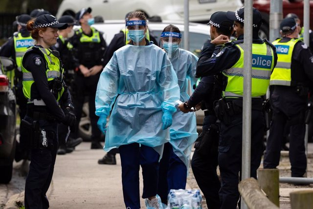 Archivo - Un grupo de agentes de la Policía de Melbourne escolta a trabajadores sanitarios, durante la crisis del coronavirus.