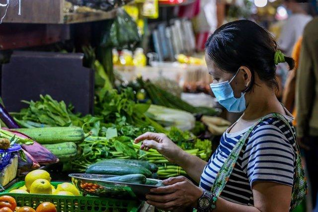Una mujer en un puesto de verduras en un mercado de Manila, Filipinas.
