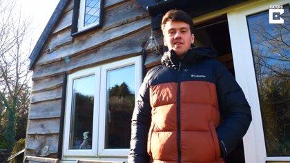 Un adolescente construye su propia casa de madera en el jardín de la casa de sus padres