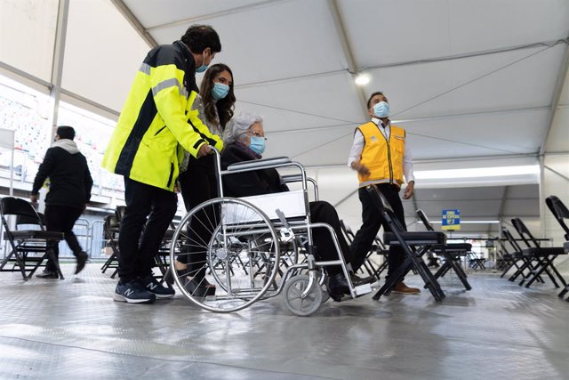 03 February 2021, Chile, Santiago: Leonila Gonzalez, 96, is taken by municipal personnel to the vaccination booth on the first day of mass vaccination, at a vaccination centre mounted at the Bicentenario Stadium. Photo: Matias Basualdo/ZUMA Wire/dpa