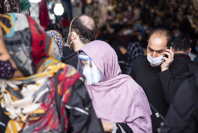 Una mujer camina por la calle con mascarilla y pantalla facial en Teherán.