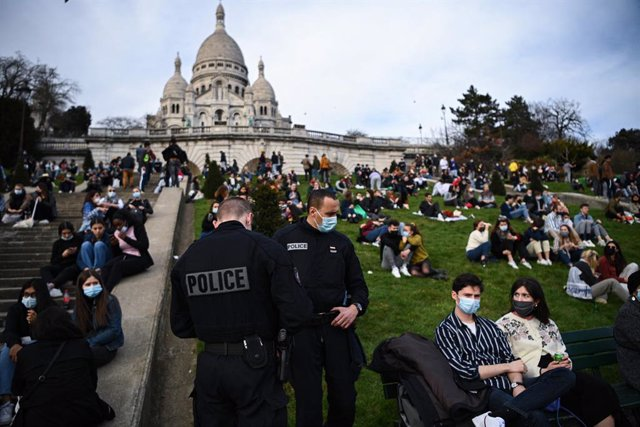 21 February 2021, France, Paris: Police officers talk to people sitting outside the Sacre Coeur Basilica. Photo: Anne-Christine Poujoulat/AFP/dpa