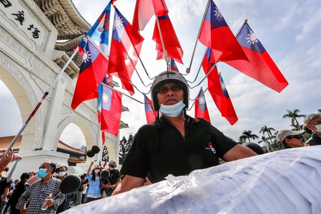 Archivo - 22 November 2020, Taiwan, Taipei: A vendor wearing a helmet with many Taiwan's national flags during a demonstration against the revoking of the operation license for CTi News, a pro Kuomintang (KMT) television company, by the National Communica