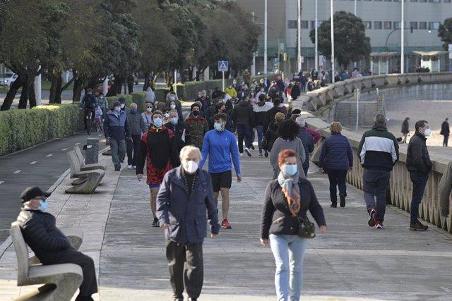 Varias personas disfrutan de un día de primavera anticipada con temperaturas de 20ºC de máxima y 11ºC de mínima en el Paseo Marítimo de la playa del Orzán en A Coruña, Galicia (España), a 16 de febrero de 2021. Tras el paso de sucesivas borrascas que han