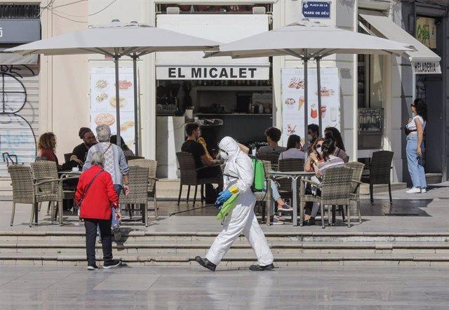 Archivo - Varias personas disfrutan en la terraza de un bar junto a la playa después de que el Ministerio de Sanidad autorizara a que la totalidad de la Comunidad Valenciana pasase en su conjunto a la fase 1