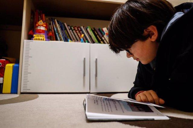 Archivo - Un niño lee en casa durante el confinamiento.