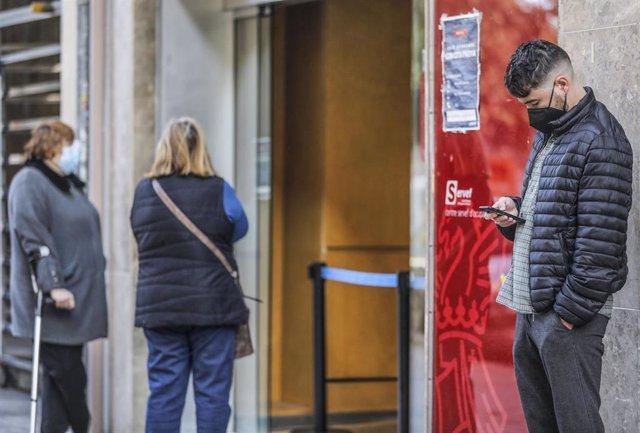Un joven mira su teléfono móvil mientras espera para entrar en una oficina del SEPE (antiguo INEM), en Valencia