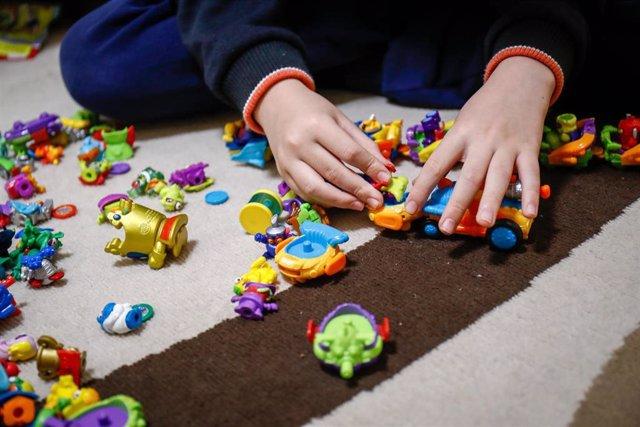 Archivo - Un niño juega en su casa con unos muñecos