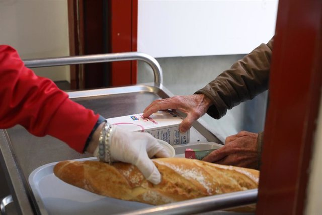 Un voluntario (i) trae comida a una persona (d) como parte del reparto diario de alimentos del Comedor Social San José, en Puente de Vallecas, Madrid (España), a 5 de febrero de 2021.