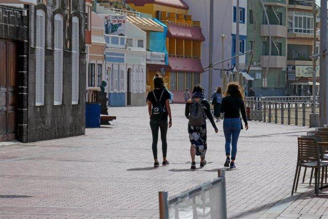 Imagen de tres jóvenes caminando por un paseo marítimo en Las Palmas de Gran Canaria
